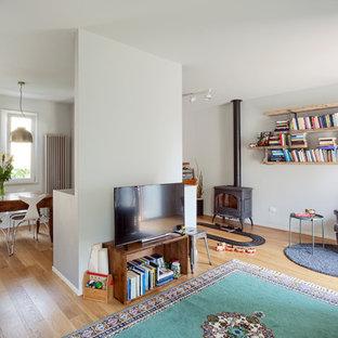 Foto di un soggiorno boho chic con pareti grigie, parquet chiaro, stufa a legna, cornice del camino in metallo, TV autoportante e pavimento beige