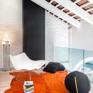 Esempio di un soggiorno bohémian stile loft con pareti bianche, parquet chiaro, camino classico, cornice del camino in metallo e sala formale