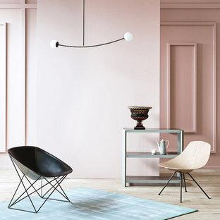Immagine di un soggiorno design chiuso con pareti rosa e parquet chiaro