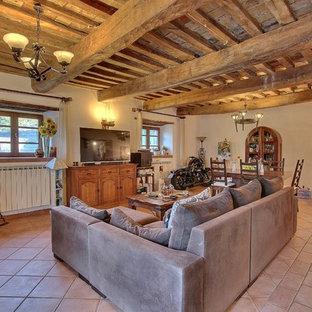 Foto di un soggiorno stile rurale con pareti beige, pavimento in terracotta, TV autoportante e pavimento rosso