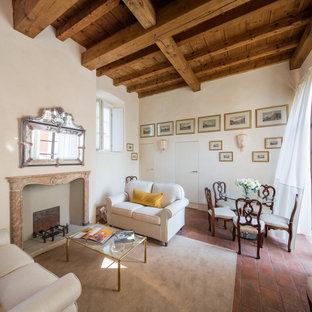 Ispirazione per un soggiorno mediterraneo di medie dimensioni e chiuso con pareti bianche, pavimento in mattoni, camino classico e cornice del camino in pietra