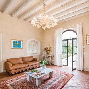На фото: изолированная гостиная комната среднего размера в средиземноморском стиле с бежевыми стенами и кирпичным полом с