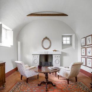 Immagine di un soggiorno mediterraneo chiuso e di medie dimensioni con pareti bianche, camino classico, cornice del camino in pietra, nessuna TV e pavimento in mattoni