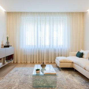 Immagine di un soggiorno design con pavimento in legno massello medio, TV autoportante, pareti bianche e pavimento marrone