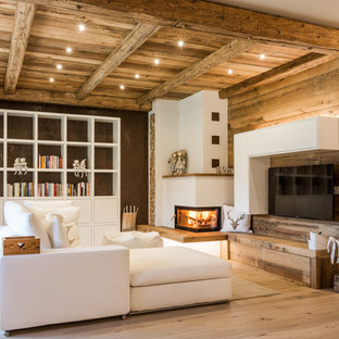 Inspiration for a mid-sized country open concept living room in Other with medium hardwood floors, a corner fireplace, a wall-mounted tv, a library, multi-coloured walls, a plaster fireplace surround and brown floor.