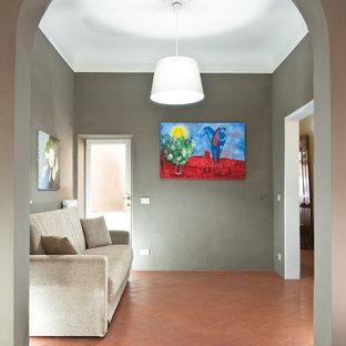 フィレンツェの小さいモダンスタイルのおしゃれなLDK (グレーの壁、テラコッタタイルの床、壁掛け型テレビ、オレンジの床) の写真