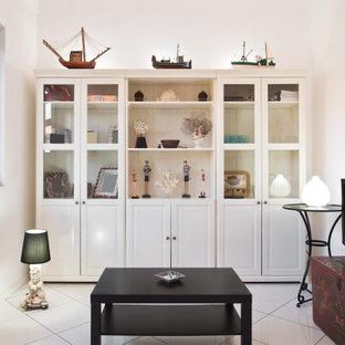 フィレンツェの小さいビーチスタイルのおしゃれなLDK (ライブラリー、白い壁、セラミックタイルの床、据え置き型テレビ、白い床) の写真