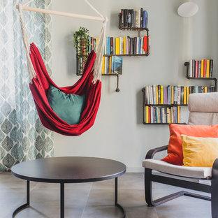 Foto di un soggiorno contemporaneo aperto con libreria, pareti grigie e pavimento grigio