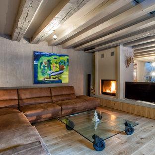 Inredning av ett industriellt mellanstort allrum, med en dubbelsidig öppen spis, en spiselkrans i gips, en fristående TV och ljust trägolv