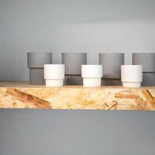 Immagine di un soggiorno minimal stile loft con angolo bar, pareti grigie, pavimento in cemento e pavimento grigio