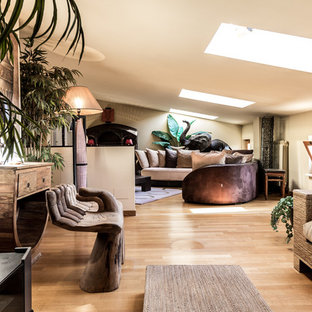 Diseño de salón para visitas abierto, tropical, grande, con paredes beige, suelo de madera en tonos medios, televisor colgado en la pared y suelo marrón