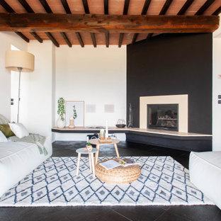 Exempel på ett medelhavsstil allrum med öppen planlösning, med vita väggar, en öppen hörnspis och svart golv