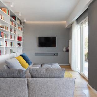 Ispirazione per un soggiorno contemporaneo con libreria, pareti grigie, pavimento in legno massello medio, camino classico, TV a parete e pavimento marrone