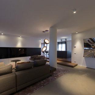 Ejemplo de salón abierto, actual, grande, con paredes blancas, suelo de cemento, televisor retractable y suelo gris