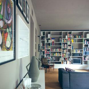 ミラノの大きい北欧スタイルのおしゃれなファミリールーム (ライブラリー、グレーの壁、淡色無垢フローリング、埋込式メディアウォール) の写真