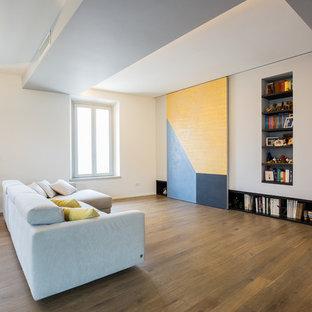 Foto di un soggiorno design aperto con libreria, pareti bianche e pavimento in legno massello medio