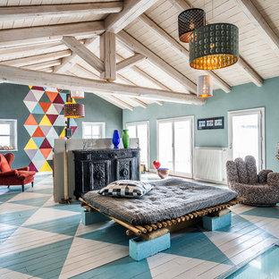 Idée de décoration pour une salle de séjour avec une bibliothèque ou un coin lecture bohème avec un mur multicolore, un sol en bois peint, un poêle à bois et un sol multicolore.