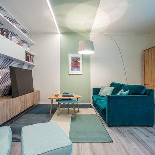 Aménagement d'un salon avec une bibliothèque ou un coin lecture contemporain de taille moyenne et ouvert avec un mur vert, un sol en linoléum, un téléviseur encastré et un sol gris.