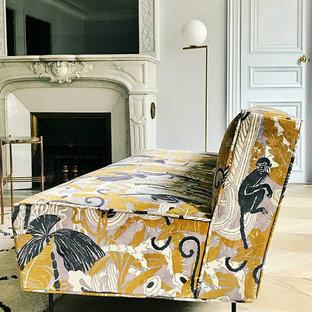 Diseño de sala de estar con biblioteca cerrada, romántica, grande, con paredes blancas, suelo de madera clara, chimenea tradicional, marco de chimenea de piedra y suelo marrón