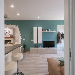 Idee per un piccolo soggiorno design aperto con pareti verdi, pavimento in linoleum, camino ad angolo, cornice del camino in intonaco e parete attrezzata