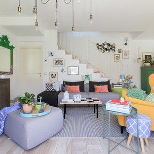 Ispirazione per un soggiorno boho chic aperto con pareti bianche, parquet chiaro e TV autoportante