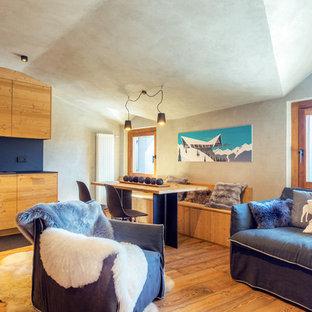 Immagine di un soggiorno rustico aperto con pavimento in legno massello medio e pareti grigie