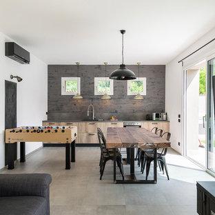 Immagine di un soggiorno industriale con sala giochi, pareti bianche, pavimento in cemento, nessun camino, TV a parete e pavimento grigio