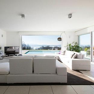 Immagine di un ampio soggiorno minimal aperto con sala formale, pareti bianche e TV autoportante