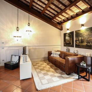 Immagine di un soggiorno mediterraneo stile loft con TV autoportante, sala formale, pareti beige, pavimento in terracotta e pavimento marrone