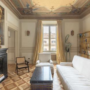 Foto di un soggiorno chic con pareti bianche, pavimento in legno massello medio, camino classico, cornice del camino in pietra e pavimento marrone