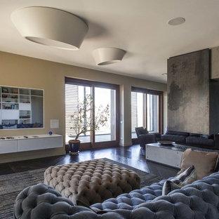 Immagine di un grande soggiorno design aperto con parquet scuro, camino bifacciale e cornice del camino in cemento