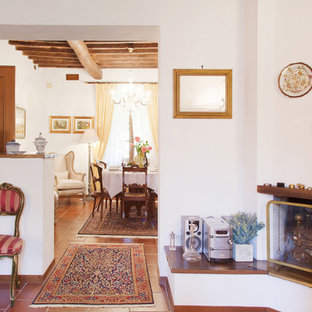 Inspiration for a timeless terra-cotta floor living room remodel in Florence with white walls, a standard fireplace and a plaster fireplace