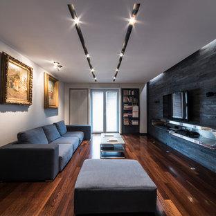 Immagine di un piccolo soggiorno contemporaneo chiuso con sala della musica, pavimento in legno massello medio, TV a parete, pareti nere e pavimento marrone