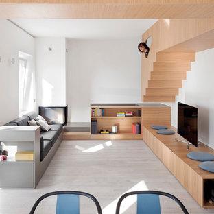 Foto di un soggiorno moderno di medie dimensioni e stile loft con pareti bianche, parquet chiaro, camino ad angolo, cornice del camino in intonaco, pavimento grigio e TV autoportante