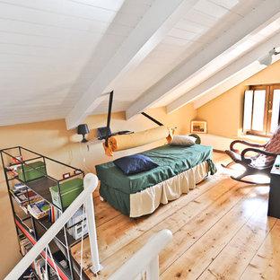 Ejemplo de sala de estar industrial, pequeña, con paredes amarillas y suelo de madera clara