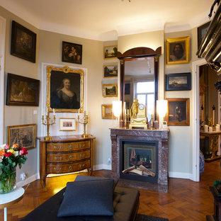 Cette photo montre un salon chic avec un mur gris, un sol en bois brun, une cheminée standard et un sol marron.