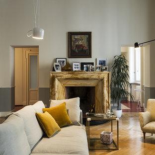 Idee per un grande soggiorno contemporaneo chiuso con pavimento in legno massello medio, camino classico e cornice del camino in pietra