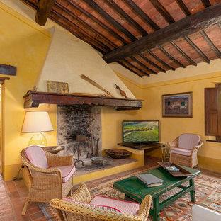 Idée de décoration pour une salle de séjour méditerranéenne fermée avec un mur jaune, un sol en carreau de terre cuite, un téléviseur indépendant et un sol orange.