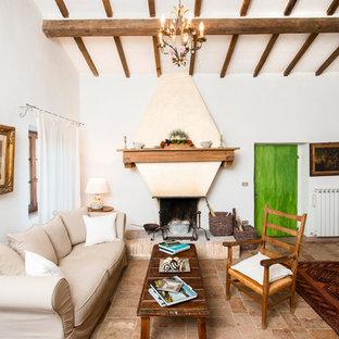 Immagine di un piccolo soggiorno country con pareti bianche, camino classico, nessuna TV e pavimento marrone