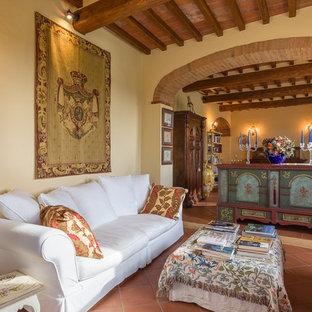 Immagine di un soggiorno mediterraneo con pareti beige, pavimento in terracotta, TV autoportante e pavimento rosso