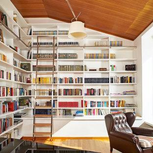 Ispirazione per un soggiorno design con libreria, pareti bianche e parquet chiaro