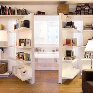 Immagine di un soggiorno contemporaneo chiuso con libreria, pareti bianche e parquet chiaro