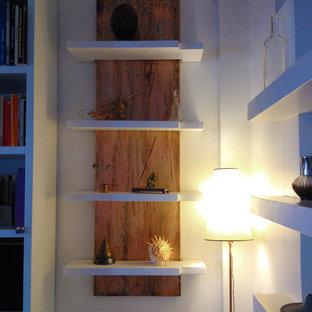 Exemple d'une petite salle de séjour avec une bibliothèque ou un coin lecture tendance fermée avec un mur blanc, un sol en ardoise et un sol gris.