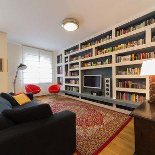 Ispirazione per un grande soggiorno bohémian aperto con libreria, pareti bianche, pavimento in legno massello medio, TV a parete e pavimento marrone