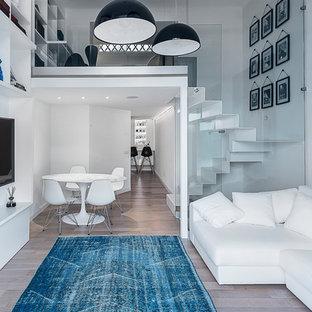 Esempio di un soggiorno contemporaneo di medie dimensioni e stile loft con pareti bianche, pavimento in legno massello medio, nessun camino e TV a parete