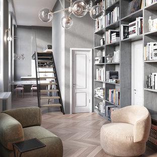 Idee per un piccolo soggiorno industriale stile loft con libreria, pareti grigie, parquet chiaro, camino lineare Ribbon, cornice del camino in metallo, TV a parete e pavimento marrone