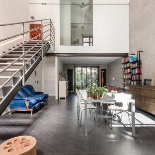 Idee per un grande soggiorno industriale stile loft con libreria, pareti multicolore, pavimento in gres porcellanato e pavimento nero