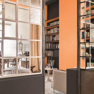 Foto di un soggiorno industriale con libreria e pareti arancioni