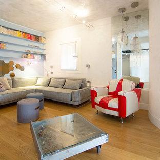 Immagine di un soggiorno bohémian di medie dimensioni con libreria, pareti multicolore, parquet chiaro e TV a parete