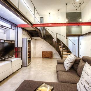 Immagine di un soggiorno industriale di medie dimensioni e stile loft con pareti bianche, pavimento in cemento, TV autoportante e pavimento grigio